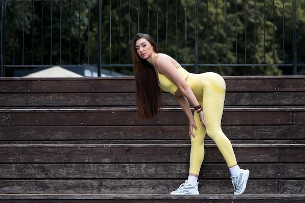 Portrait d'une femme aux muscles gonflés. belle femme sportive posant dans les escaliers dans le parc de la ville. fitness, musculation, concept d'aérobic.