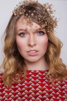 Portrait d'une femme aux yeux bleus avec des perles sur sa tête. le modèle montre des accessoires, des bijoux