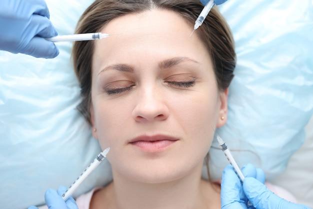 Portrait de femme aux yeux fermés recevant plusieurs injections de beauté