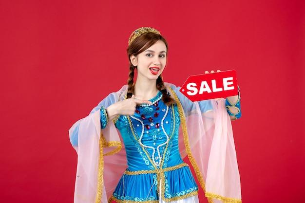 Portrait de femme azérie en costume traditionnel tenant la plaque signalétique de la vente sur le rouge