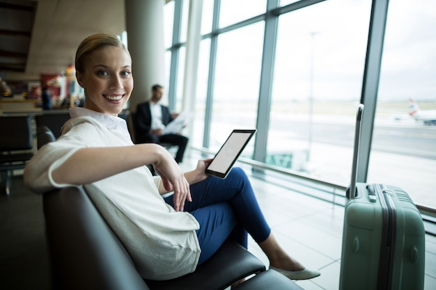 Portrait de femme de banlieue avec tablette numérique assis dans la zone d'attente