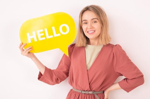 Portrait de femme bavarde souriante tenant hello tag, elle communique sur internet