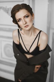 Portrait de femme beau modèle avec coiffure tendance et maquillage professionnel de soirée. vue latérale d'une fille à la mode avec des lèvres tendres et des yeux charbonneux posant dans un intérieur de luxe.