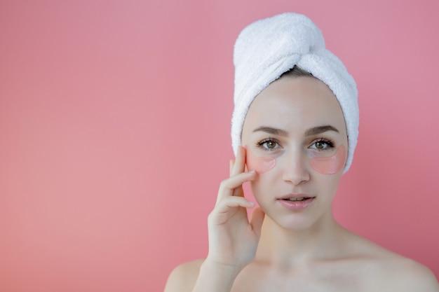 Portrait de femme de beauté avec des correctifs oculaires sur fond rose. visage de beauté femme avec masque sous les yeux. soins de la peau, concept de produit cosmétique avec espace copie
