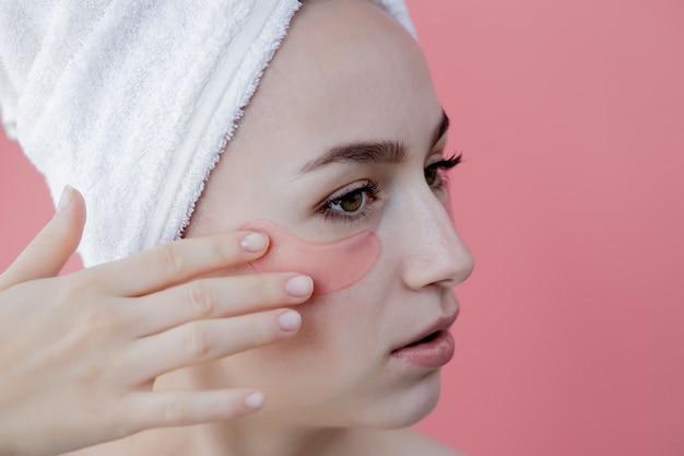 Portrait de femme de beauté avec des correctifs oculaires sur fond rose. visage de beauté femme avec masque sous les yeux. soins de la peau, concept de produit cosmétique
