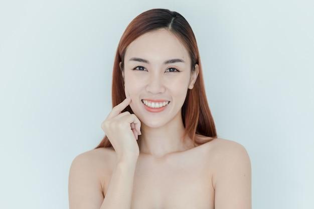Portrait de femme beauté. magnifique modèle de spa girl avec une peau parfaitement fraîche et nette. brunette femme regardant la caméra et souriant. concept jeunesse et soins de la peau
