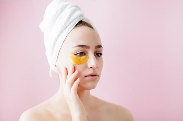 Portrait de femme de beauté avec des patchs oculaires sur rose