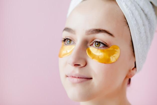 Portrait de femme de beauté avec des patchs pour les yeux sur l'espace rose