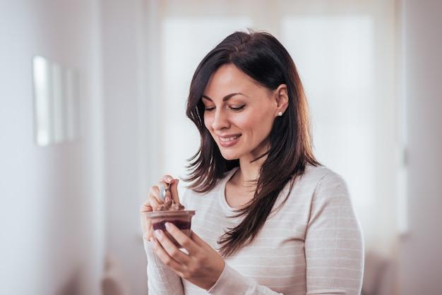 Portrait d'une femme belle femme manger du pouding au chocolat.