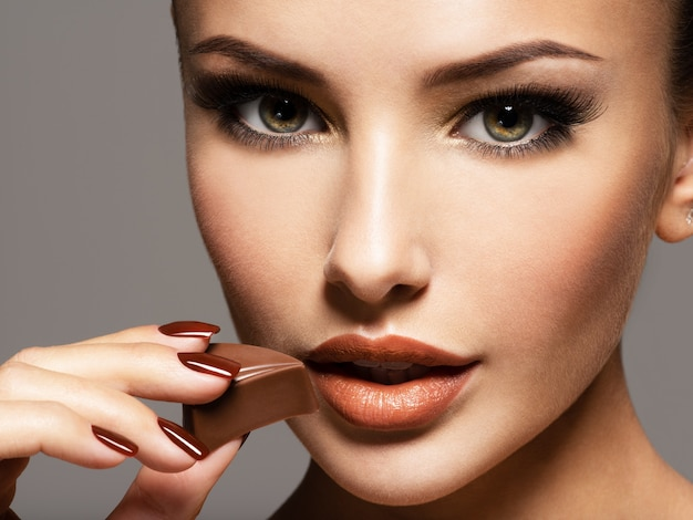 Portrait de femme belle glamour tient et mange des bonbons au chocolat. photo dans le style de couleur marron