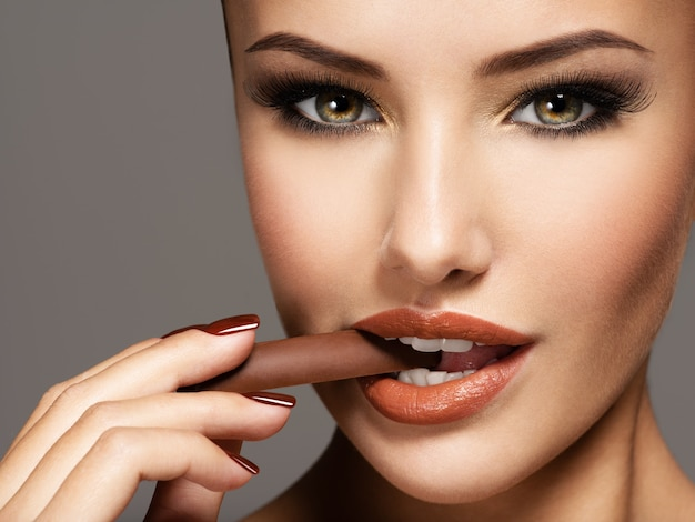 Portrait de femme belle glamour tient et mange des bonbons au chocolat.