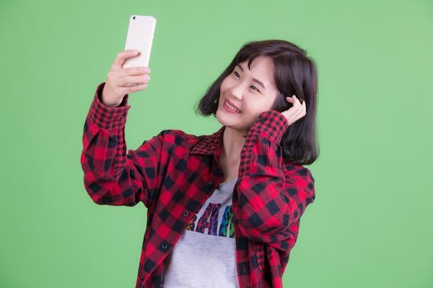 Portrait de femme belle hipster asiatique aux cheveux courts contre clé chroma ou mur vert