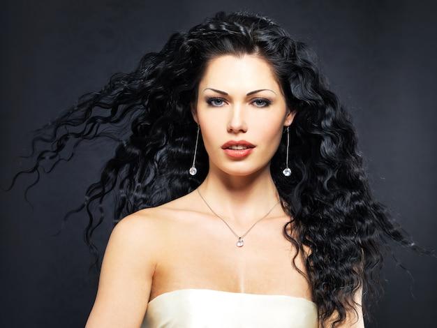 Portrait de la femme belle mode avec une longue coiffure frisée pose à l'intérieur