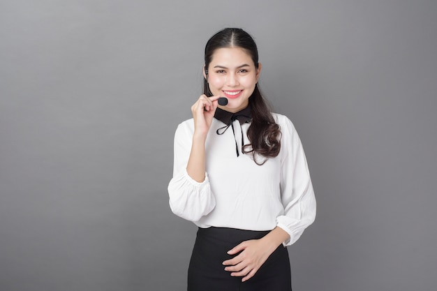 Portrait de femme belle opérateur sur mur gris