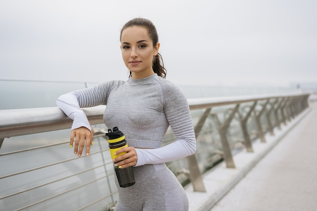 Portrait de femme belle remise en forme en tenue de sport élégante tenant une bouteille d'eau, debout à l'extérieur