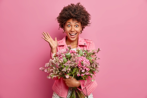 Portrait de femme belle soulève la paume réagit aux félicitations inattendues a date avec petit ami détient grand bouquet de fleurs isolé sur mur rose