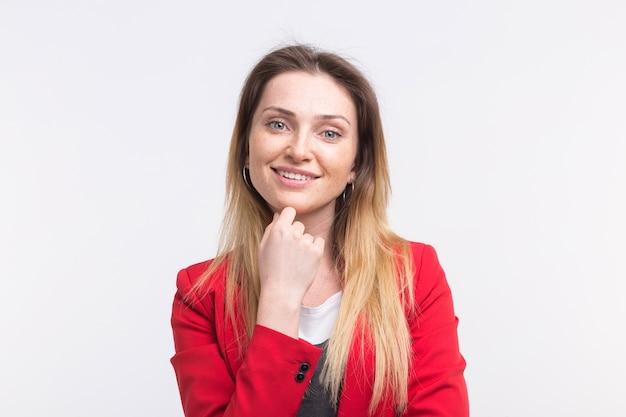 Portrait de femme belle de taches de rousseur souriant avec la main sur son menton, vêtu de rouge