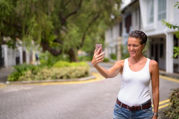 Portrait de femme belle touriste mature profitant de la vie lors d'un voyage dans la ville de singapour
