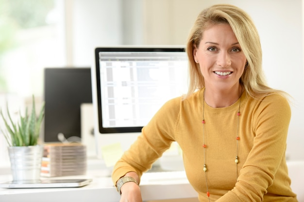 Portrait d'une femme blonde d'âge moyen au bureau