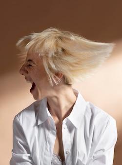 Portrait de femme blonde aux cheveux courts posant dans une chemise blanche