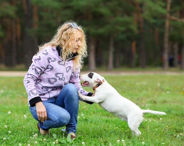 Portrait d'une femme blonde avec un chien dans le parc