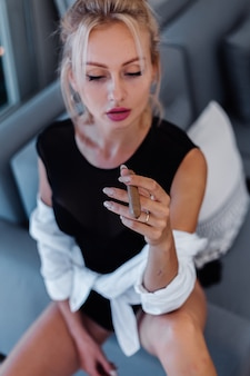 Portrait de femme blonde en costume de corps et chemise blanche avec de belles lèvres roses tenant un cigare