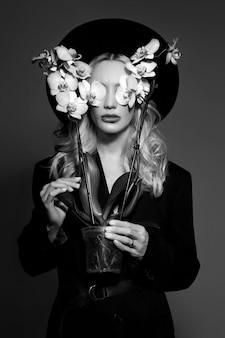 Portrait d'une femme blonde dans un grand chapeau noir rond, une fleur d'orchidée dans ses mains