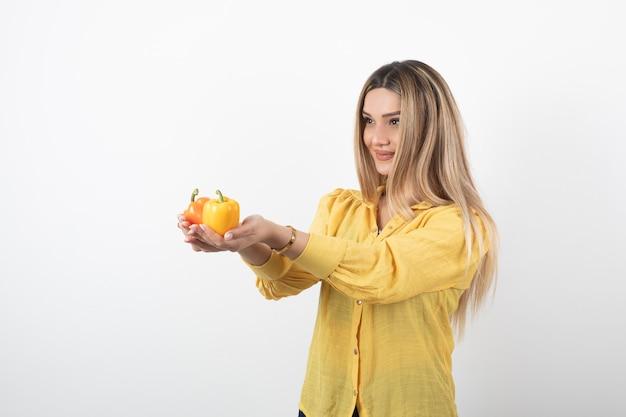 Portrait de femme blonde donnant des poivrons colorés sur un mur blanc.