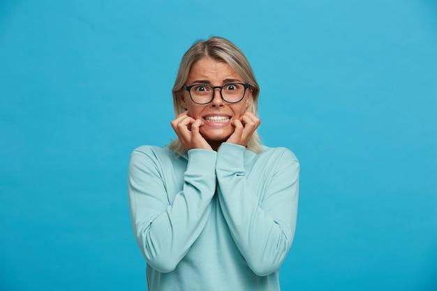 Portrait de femme blonde effrayée, a l'air effrayé peur de claquer des dents avec peur