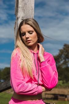 Portrait d'une femme blonde. elle est au soleil, vêtue de rose. concept d'automne et extérieur.