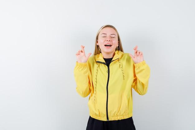 Portrait de femme blonde en gardant les doigts croisés en survêtement et à la vue de face heureuse