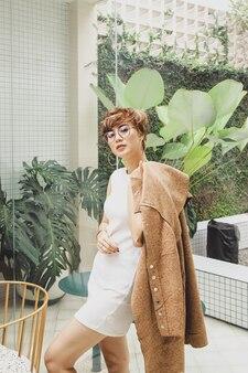 Portrait de femme blonde glamour en robe blanche posant tout en tenant un manteau