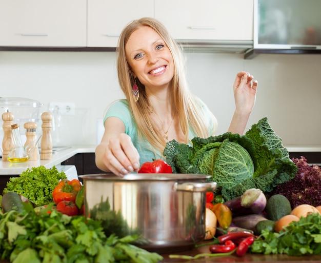 Portrait de femme blonde heureuse avec des légumes