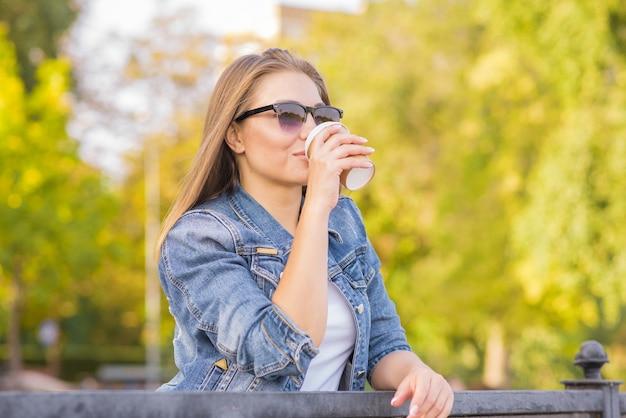 Portrait d'une femme blonde jeune, heureuse et belle qui boit du café