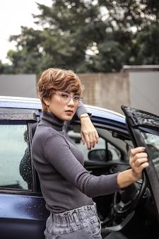 Portrait de femme blonde à lunettes posant avec voiture