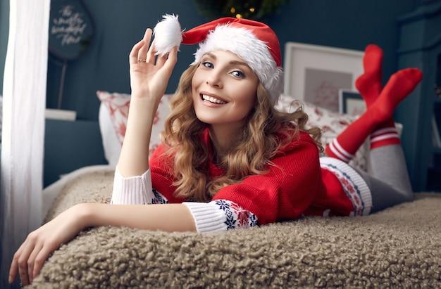 Portrait de femme blonde magnifique en pull rouge et bonnet de noel s'amusant dans son lit et posant dans l'intérieur décoré de noël.