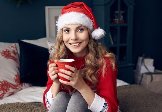 Portrait de femme blonde magnifique en pull rouge et bonnet de noel avec une tasse de café posant dans l'intérieur décoré de noël.