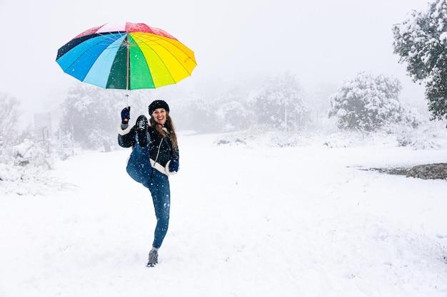 Portrait de femme blonde avec parapluie de couleur lançant un coup de pied de karaté lors d'une chute de neige.