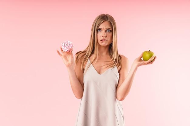 Portrait d'une femme blonde perplexe portant une robe hésitant tout en tenant un beignet sucré et une pomme verte isolée sur un mur rose en studio