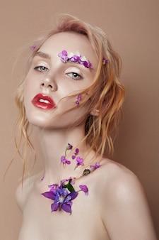 Portrait femme blonde avec des pétales de fleurs sur son visage agrandi, maquillage lumineux et rouge à lèvres. hydratation de la peau, soins du visage, effet anti-âge des cosmétiques. extrait de fleur cosmétique naturelle, beauté et mode