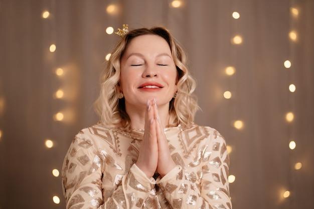 Portrait de femme blonde avec une petite couronne sur la tête avec les yeux fermés fait un vœu avec ses mains jointes devant son visage.