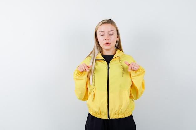 Portrait de femme blonde pointant vers le bas en survêtement et à la vue de face curieuse