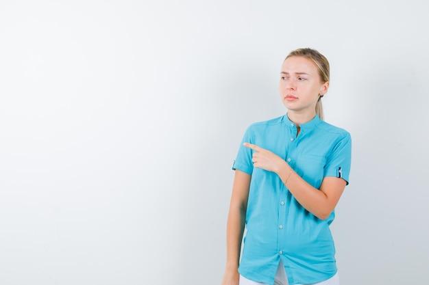 Portrait de femme blonde pointant vers la gauche en blouse bleue isolée