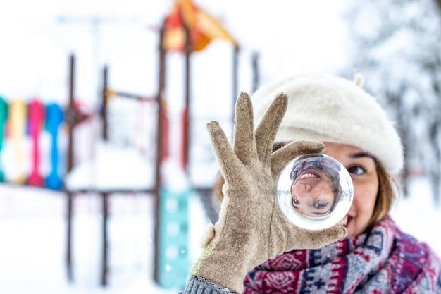 Portrait d'une femme blonde portant un béret, une veste et une écharpe tenant dans sa main une boule de cristal dans un parc enneigé.