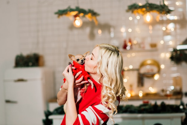 Portrait de femme blonde portant noël santa tenant des chiens chihuahua en costume de noël dans la cuisine avec décoration de noël, souriant et regardant la caméra.