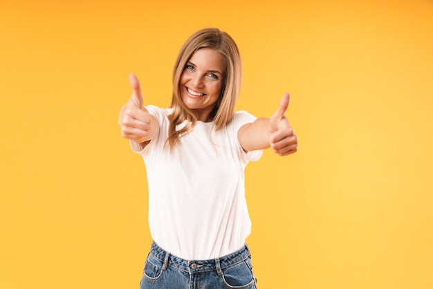 Portrait d'une femme blonde portant un t-shirt décontracté souriant à l'avant et montrant les pouces vers le haut isolé sur un mur jaune en studio