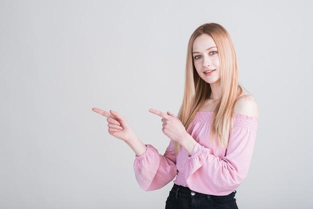 Portrait d'une femme blonde qui pointe ses doigts vers le studio sur fond blanc