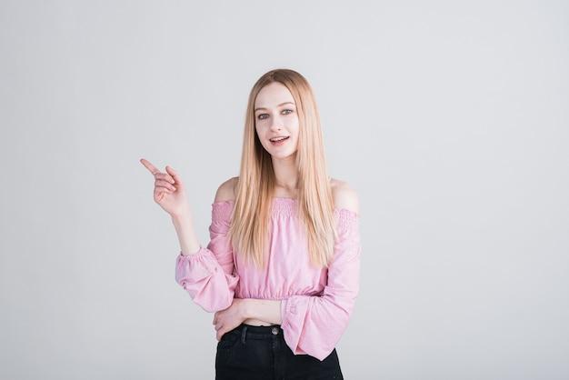 Portrait d'une femme blonde qui pointe son doigt