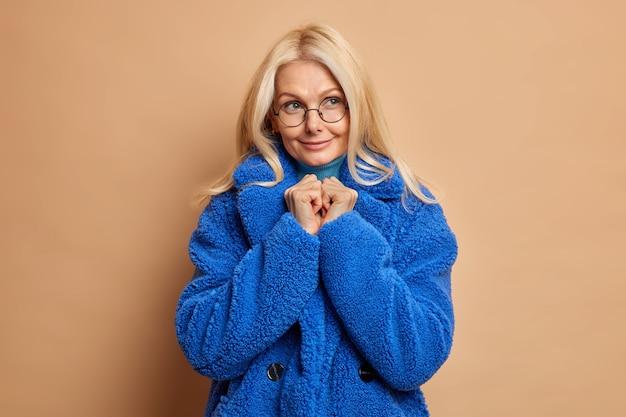 Portrait de femme blonde à la recherche agréable garde les mains jointes et regarde ailleurs porte des lunettes optiques rondes manteau de fourrure bleu prêt pour la marche hivernale.