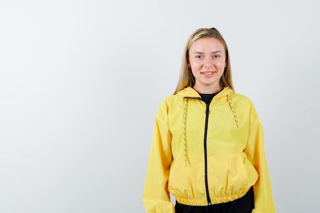 Portrait de femme blonde regardant la caméra en survêtement et à la joyeuse vue de face